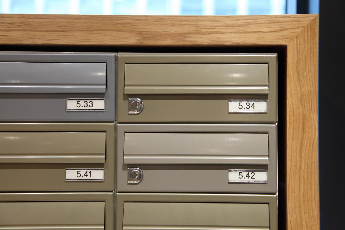 Multiple freestanding postboxes with bespoke timber surround for student accommodation